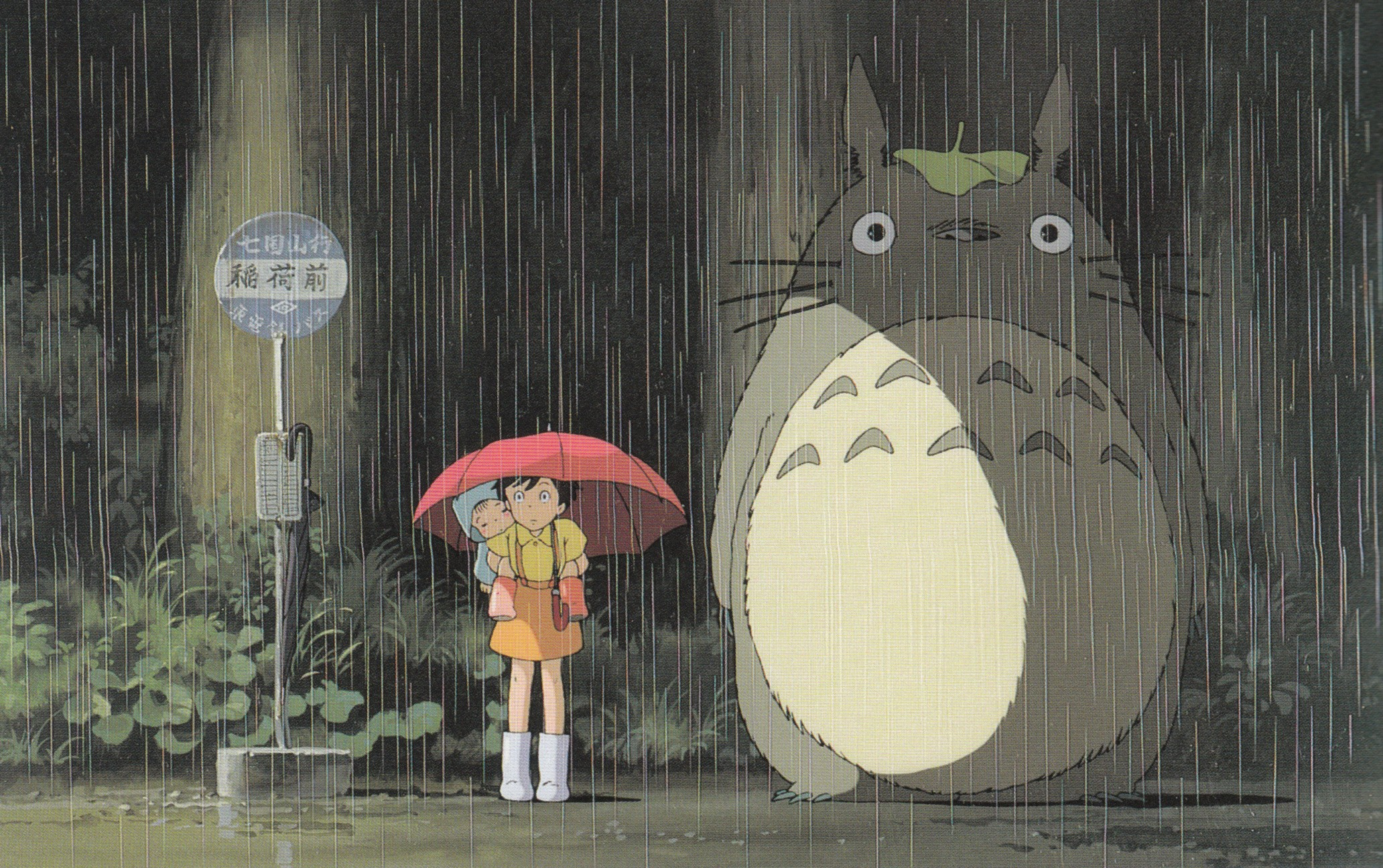 The most iconic scene from My Neighbor Totoro: a huge grey and white bear-like creature waits at a rainy bus stop with two children