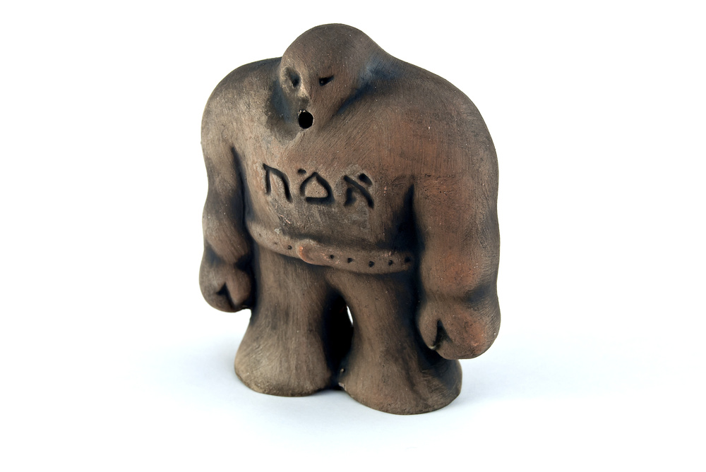 "A clay figure of the golem of Prague, with emet (""truth"") written on its chest."