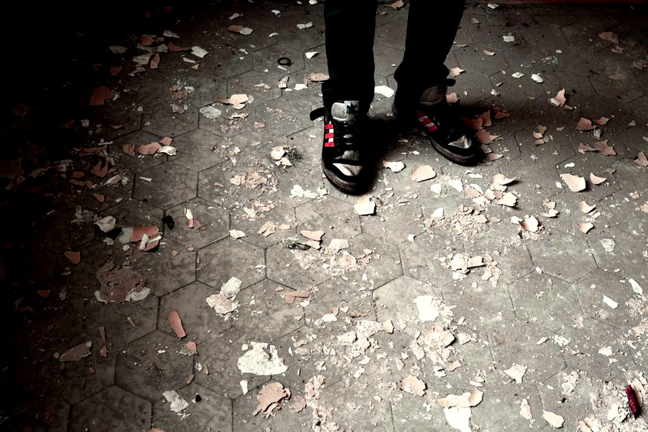 A person's feet surrounded by broken debris